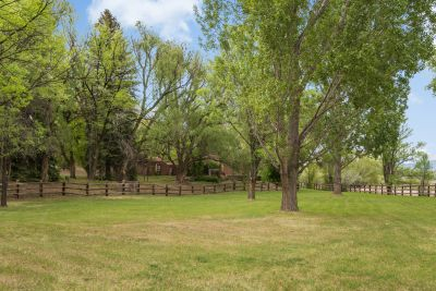 Green Lawns, Trees, and Fencing Line the Property