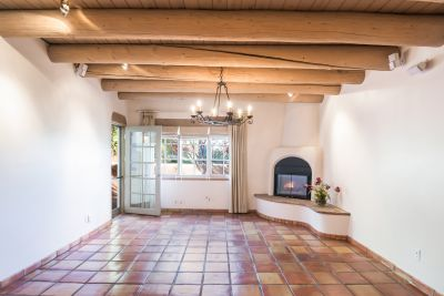 Living Room with Gas Kiva Fireplace and Access to Portal and Enclosed Patio