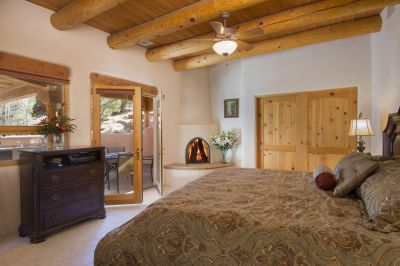 Guest Bedroom One with Wood-burning Fireplace Accesses Entertainment Portal and Patio