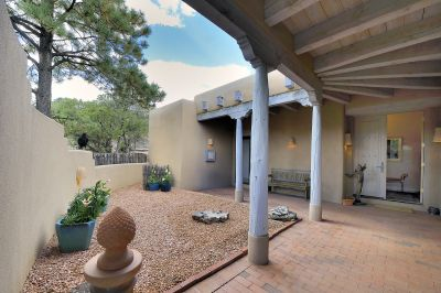 The courtyard with bricks, high ceilings, and Santa Fe Style columns and corbels.