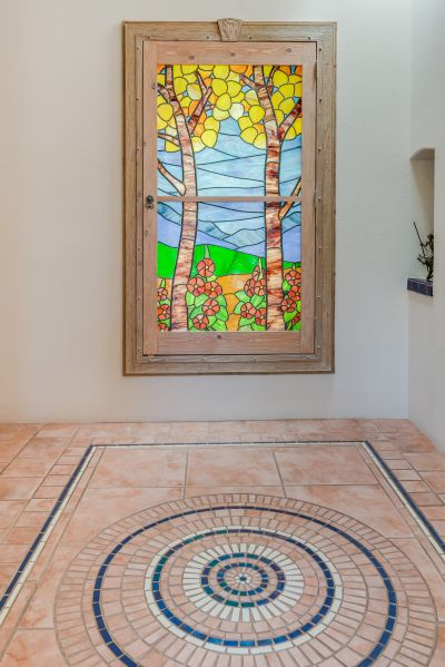 Inside, a lit stained glass window and mosaic floor greet your guests.