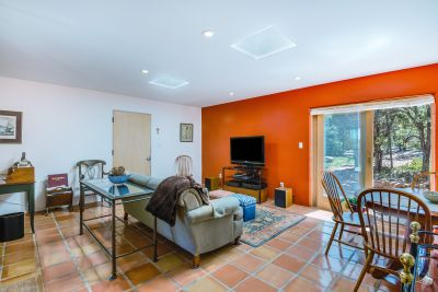 Family/Media Room - Saltillo tile floor and wide sliding door to forested and wildflower-strewn grounds.