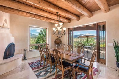 Dining Room with Double-sided Kiva Fireplace Opens to the Dining Portal and Patio