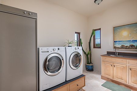 Primary Laundry in Master Suite: LG Washer & Dryer and Asko Cabinet Dryer. Custom laundry pedestal, cabinets and sink.