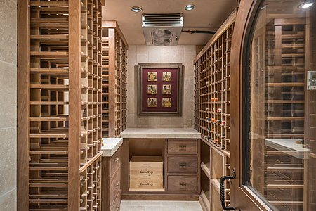 Wine Room. Dual-stage cooling systems, walnut racks and stone-clad walls.