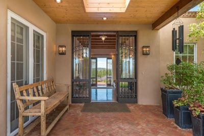 Custom Cantera Wrought Iron Door and Sidelights Frame the Elegant Entry
