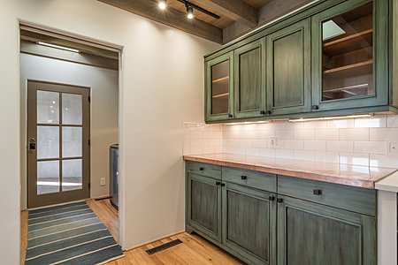 Handsome copper serving counter and butler's pantry grace the kitchen entrance...