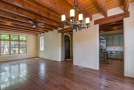Living room in newer home with wood floors and beam ceilings.