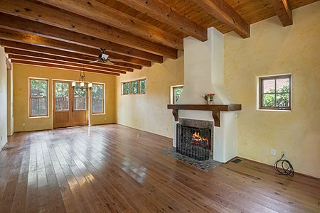 View of Living room and Dining room with wood burning fireplace.