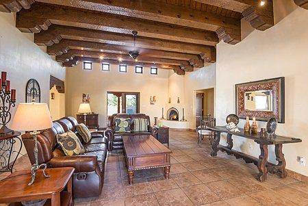 Great Room featuring high ceiling with Beams, Corbels, tile flooring and plaster walls.