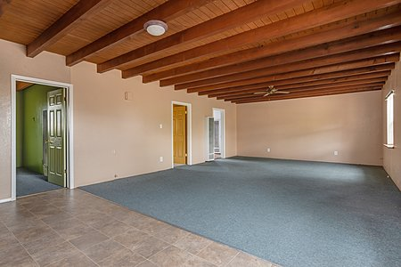 Large great room with living room, dining room and kitchen with beam ceilings
