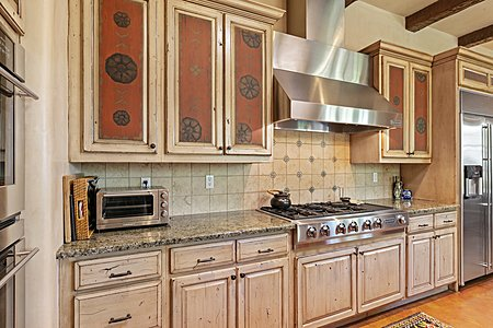 ...a Six-burner Cooktop with Griddle and Abundant Custom Cabinets