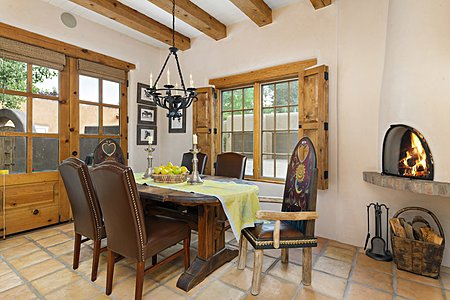 Dining Area w/ Cozy Fireplace & French Doors to Entry Courtyard