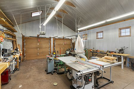 Dual garage doors lead to a spacious workshop area