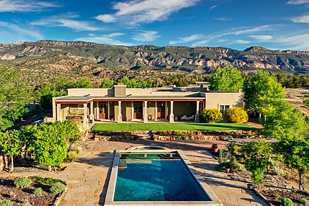 Adobe hacienda main house with a pool and National Forest in the background
