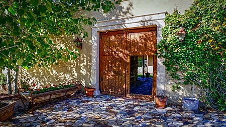 Cobblestone front entrance through custom wooden doors leading to the main house placita