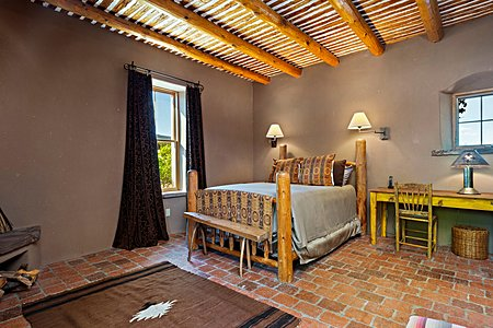 The detached guest suite has a private entrance with brick floors, kiva fireplace, and a bathroom