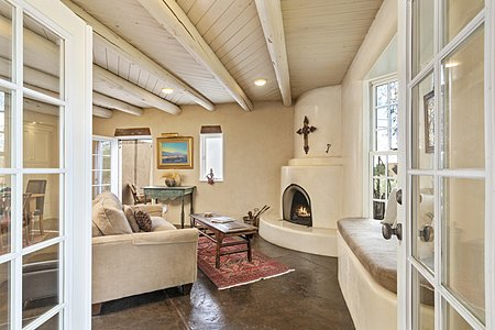 Living Room with Plaster Walls and Beamed Ceilings