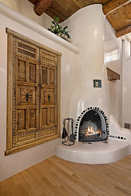 Kiva fireplace in informal dining room with media cabinet at left