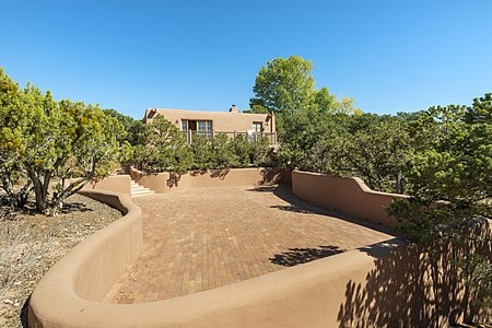 Paved parking area with casita in distance on property